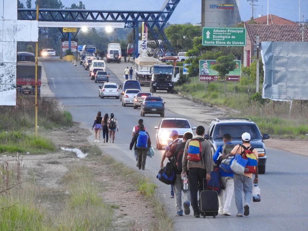 Foto de imigrantes da Venezuela atravessando a fronteira